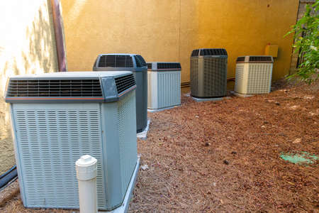 Multiple Air Conditioner Compressors next to large house or building, with room for copy space Archivio Fotografico