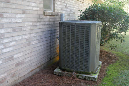 Air Conditioner Unit next to gray brick wall of house