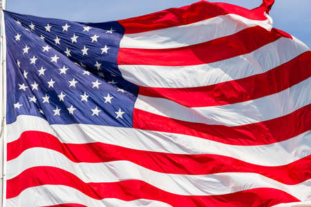 Large beautiful American flag waving in the wind, with vibrant red white and blue colors, filling the frame.