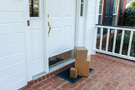 Shipping boxes on front porch of home Archivio Fotografico