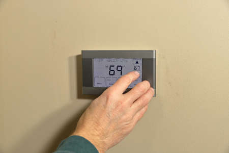 Hand adjusting temperature on digital programmable thermostat