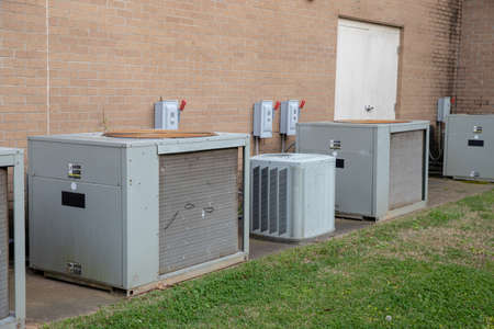 Multiple Commerical Air Conditioner Compressors outside brick building Stock Photo
