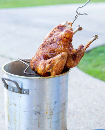Pulling a whole deep fried turkey out of the fryer