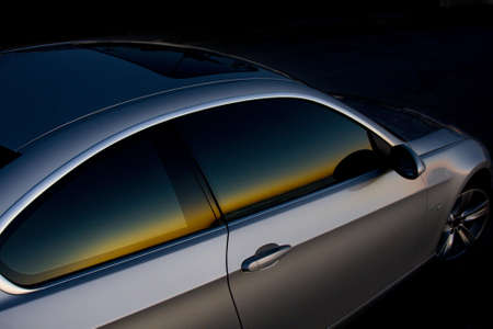 Sunset colors reflecting in the passenger window of a sports car.