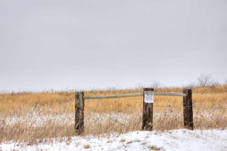 Wooden fence in field with posted no trespassing sign attached photo