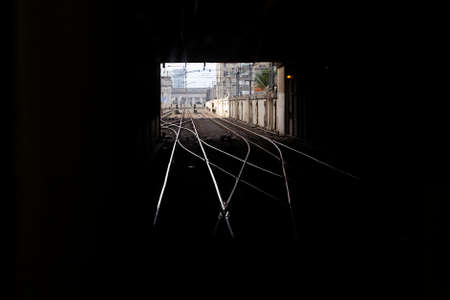 vanish: Train tracks leading out from a tunnel Stock Photo