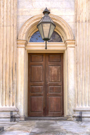 transom: A wooden door closed in a marble entryway with a glass transom and overhead light