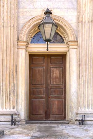 puertas de madera: Una puerta de madera cerrada en una entrada de mármol con un espejo de popa de vidrio y luz cenital