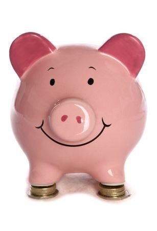 pound coins: Piggybank resting on pound coins studio cutout