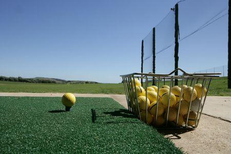 Pelota de golf y la cuchara en el driving range  Foto de archivo