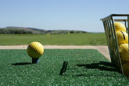 Golf ball and bucket at driving range photo