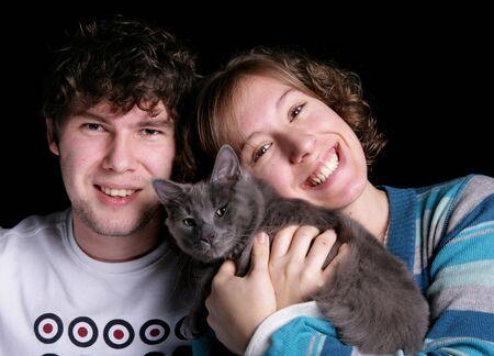 dos personas con una catAdult macho y hembra adultos con una catstudio gris