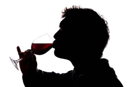 赤ワインのシルエットのガラスを飲む男性 写真素材