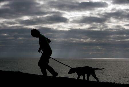 少年と犬のビーチ シルエットの上を歩いて 写真素材