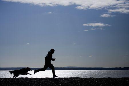 Hombre que se ejecutan con perro en silueta de playa Foto de archivo