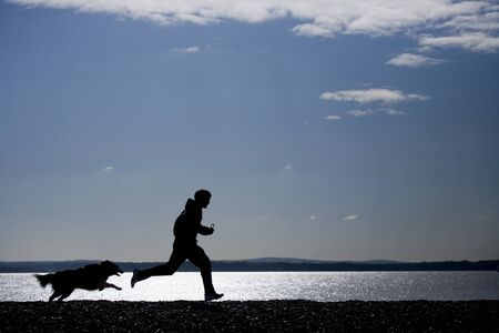 Man running with dog on beach silhouette