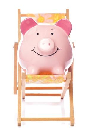 Piggy bank on deck chair studio cutout photo