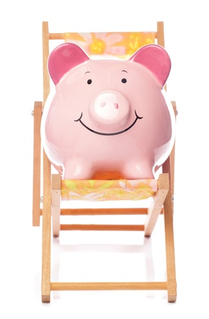 Piggy bank on deck chair studio cutout photo
