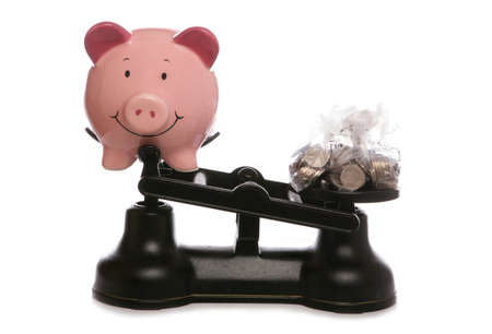 Piggy bank on scales with sterling money studio cutout Stock Photo - 9190636