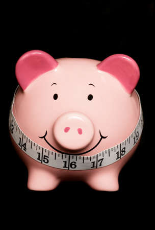Piggy bank with tape measure isolated on black photo