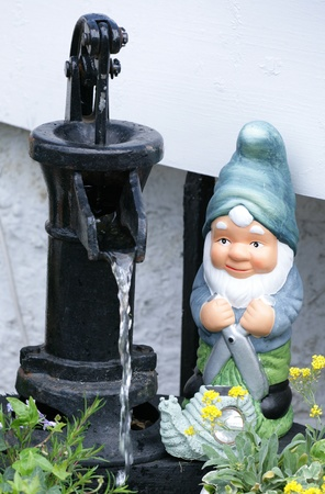 water feature: garden gnome by water feature Stock Photo