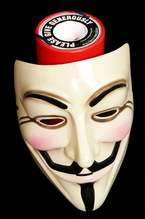 guy fawkes mask: Guy fawkes mask with cahrity collection on black background Editorial