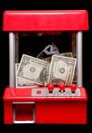 american money: American money in a grabbing machine on black background Stock Photo