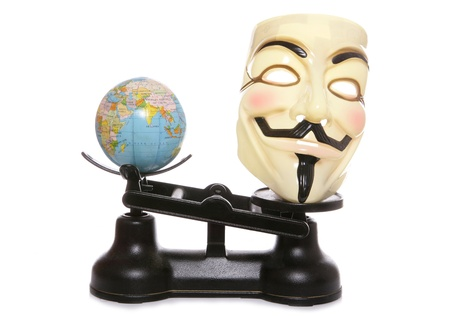 guy fawkes mask: Guy fawkes mask on scales with a globe studio cutout Editorial