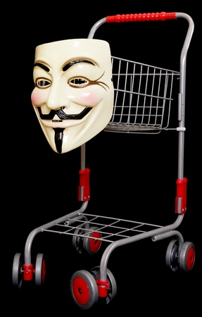 guy fawkes mask: Guy fawkes mask with a shopping trolley on black background Editorial
