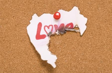 heartbroken: Heart shape burnt paper on corkboard