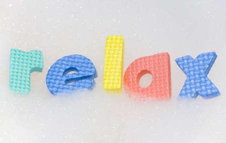 destress: relax letters in bubble bath foam abstract