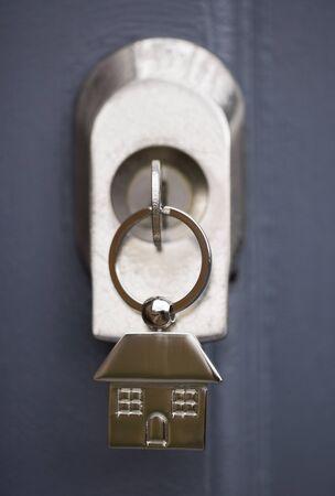 keyring: House keys and keyring in a grey door abstract