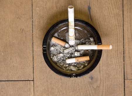 burning money: cigarettes and ten pound note in an ash tray Stock Photo
