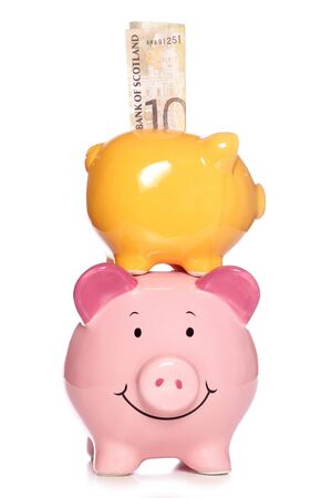 Piggy banks with Scottish money studio cutout photo