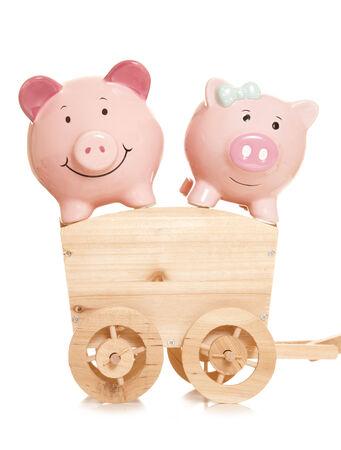 piggybanks: two piggybanks on a wooden cart cutout Stock Photo