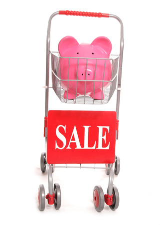 sale sign: shopping trolley with piggy bank and sale sign cutout Stock Photo