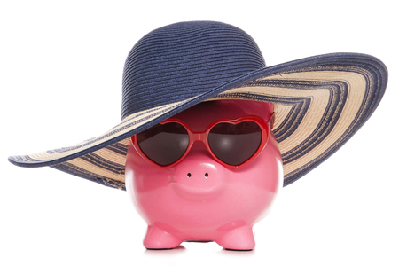 white piggy bank: piggy bank wearing a sun hat and sunglasses cutout Stock Photo