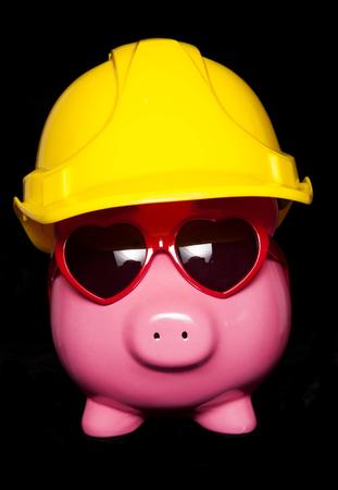 hard hat: piggy bank wearing hard hat black background