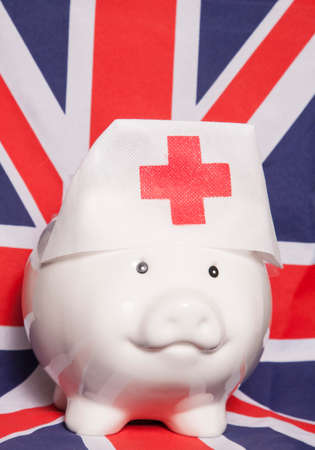 health care funding: piggy bank wearing nurse hat on british flag Stock Photo