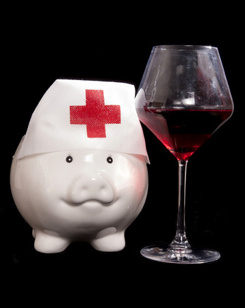 nhs: piggy bank nurse with red wine cutout Stock Photo