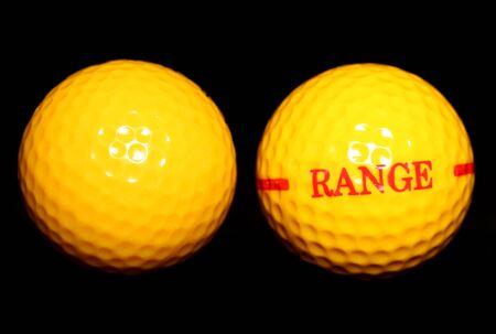 driving range: two yellow driving range golf balls on black background