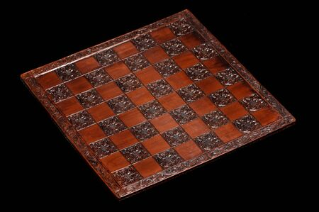chess board: Ornate wooden chess board on black background Stock Photo