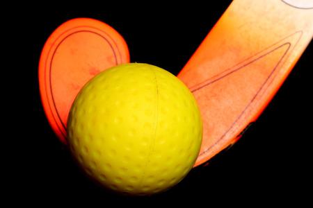 ホッケー ボールと黒の背景上の棒