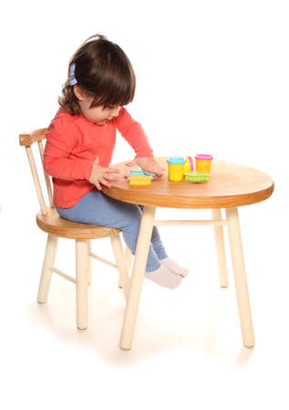 toddler girl playing with play doh Stock Photo