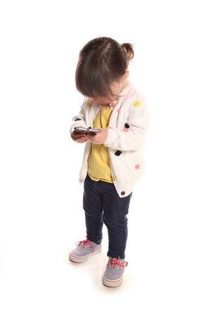 携帯電話で 2 歳の幼児プレイ 写真素材