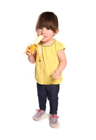 スタジオでバナナを食べる 2 歳の幼児