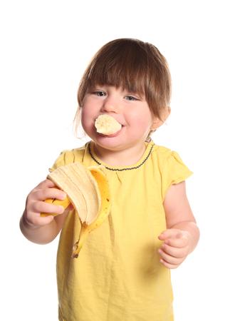 スタジオでバナナを食べる2歳の幼児 写真素材
