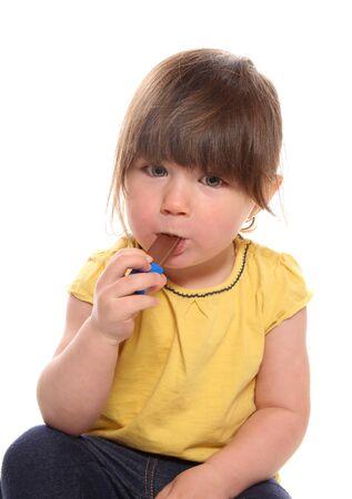 スタジオでチョコレートを食べている2歳の少女