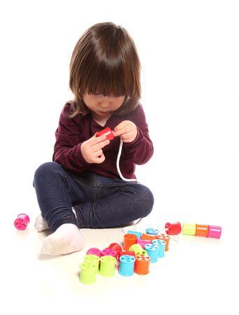 スタジオでコットンリールで遊んでいる2歳の少女