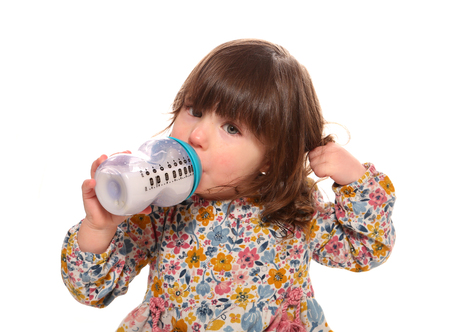 toddler girl drinking milk from a bottle 写真素材